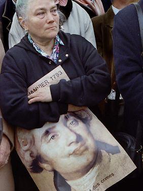 Frau mit einem Bild von König Ludwig XVI. bei einer Gedenkfeier auf dem Place de la Concorde in Paris anlässlich des 200. Jahrestages seines Todes durch die Guillotine, am 21. Januar 1993.
