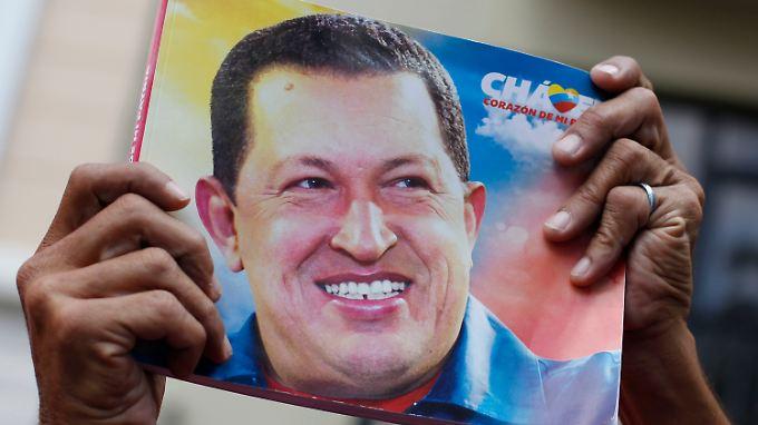 Ein Unterstützer des Präsidenten reckt ein Bild in die Höhe.