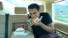 Auf dem Weg in die Stadt isst er einen Burger.