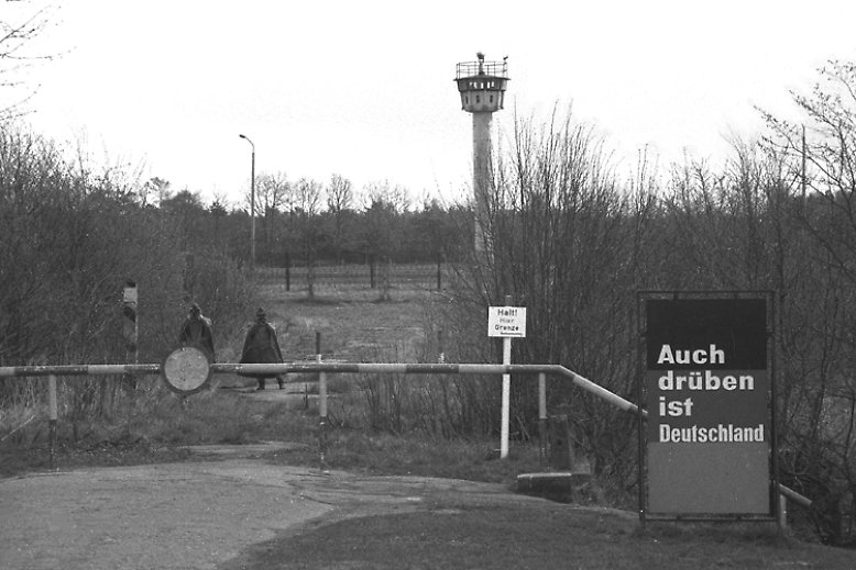 Eicholz nahe Lübeck, 1984: Mahnend steht das Schild vor dem Grenzstreifen mit Wachturm und erinnert mit anklagender Sachlichkeit daran, dass das Land hier eigentlich noch weitergeht. Auf der anderen Seite liegt Herrnburg in Mecklenburg-Vorpommern.