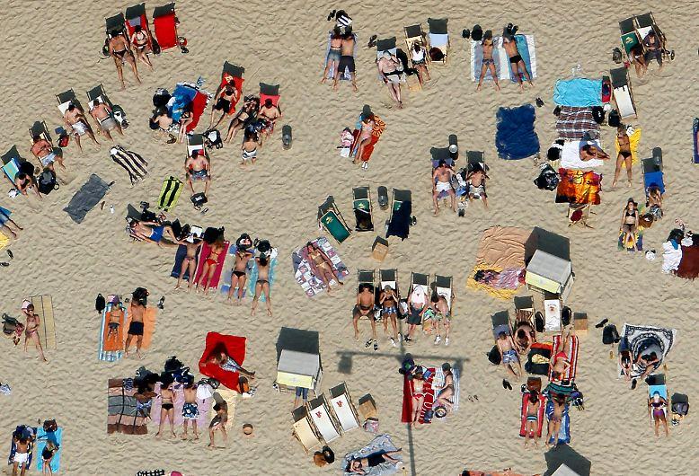 Ein typischer Tag am Strand: Die Sonnenanbeter gehen liegend auf die Jagd nach dem perfekten Teint, ...